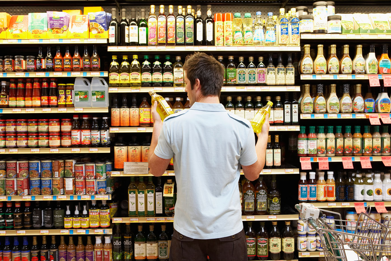 Man examining product packaging at a supermarket
