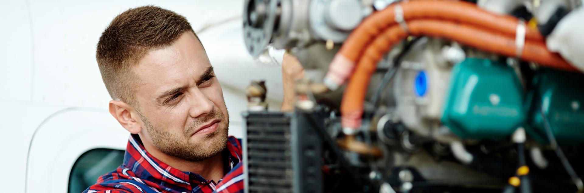 MRO: Mechanic works on aircraft engine.